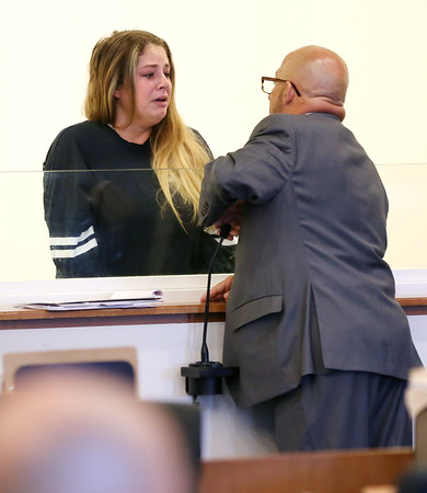 KEN YUSZKUS/Staff photo.    Emma Wiley talks with her attorney Mark Barry. She is the 19-year-old arraigned in Salem District Court for biting off a piece of a Salem police officer's ear.    08/08/16