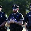 DAVID LE/Staff photo. Officers Jeffrey Aceituno and Robert Mason, of Lynn, left, and Officer Steven Luck, of Swampscott, stand at attention during the playing of taps at the end of the short flag folding ceremony on Sunday evening. 8/7/16.