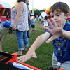 DAVID LE/Staff photo. Ryan McElroy, of Salem tosses bean bags that smash through row of tin cans at the first annual National Night Out hosted by the Salem Police Department at the Salem Commons on Tuesday evening. 8/2/16.