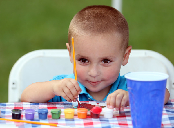 DAVID LE/Staff photo. Two-year-old Zachary Colwell, of Salem, smiles while painting at Kid's Night as part of the Heritage Festival at Salem Common. 8/12/16.
