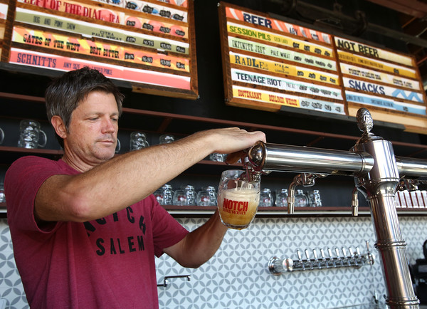 KEN YUSZKUS/Staff photo   One of Notch's founders, Chris Lohring pours a beer from a specially designed tap from the Czech Republic of Pilsen at the bar.  08/17/16