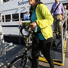 KEN YUSZKUS/Staff photo.  Commuter Jeanne Carey disembarks with her bicycle in Boston after arriving on the Salem Ferry.   08/03/16