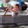 DAVID LE/Staff photo. Ten-year-old Will Fogelgren, of Beverly, paddles his boat toward the finish line of the cardboard boat races on Sunday afternoon. 8/7/16.