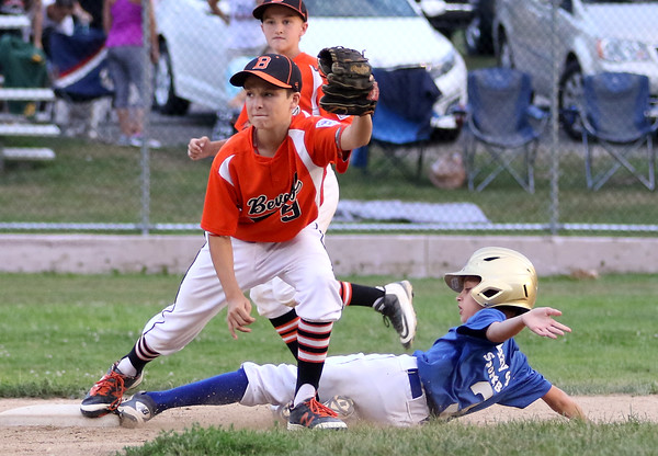 DAVID LE/Staff photo. Beverly shortstop Griffin Francis stretches to get a force out on a sliding Lynn runner at second base. 8/17/16.