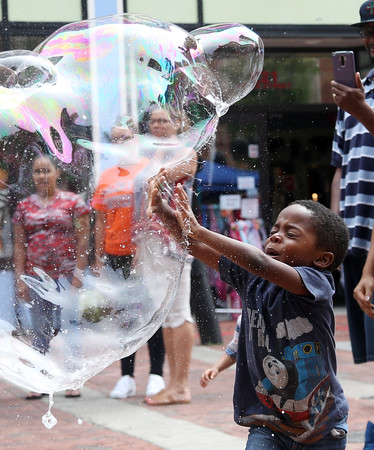 DAVID LE/Staff photo. Three-year-old Zayne Carle-Doyle, of Boston, happily pops a large bubble on Saturday afternoon during the Essex Street Pedestrial Mall fair. 8/13/16.