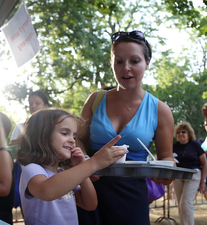 DAVID LE/Staff photo. Five-year-old Evelyn Loux, of Salem, carefully places a cup of ice cream on a muffin tray carried by her mom Colette, at the annual Ice Cream Bowl at Salem Common. 8/9/16.