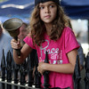 DAVID LE/Staff photo. Ten-year-old Sofia Iglesias rings a bell to signal a premium lap during the Women's Elite race of the annual Witches Cup on Wednesday evening. 8/10/16.
