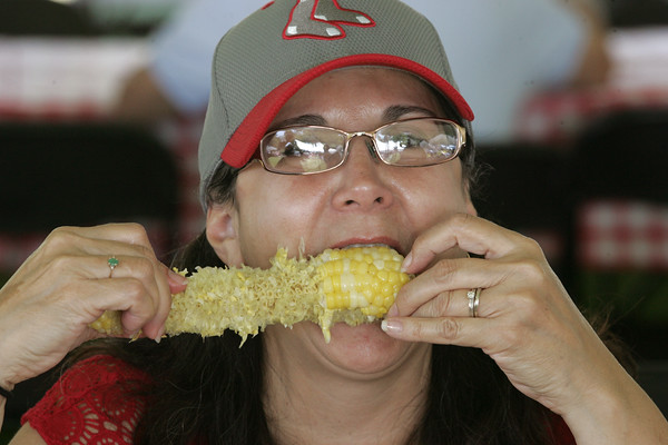 KEN YUSZKUS/Staff photo.    Jeannie Jeness, originally from Beverly and now from Florida, eats corn on the cob at the Lobster Festival held at Lynch Park.  08/03/16