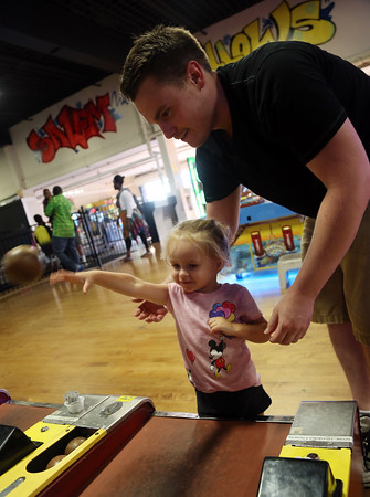 DAVID LE/Staff photo. Two-year-old Gianna Dixon, of Peabody, plays skeeball with help from her uncle, Luke Raphael, at the Salem Willows Arcade on Tuesday evening. 8/30/16.