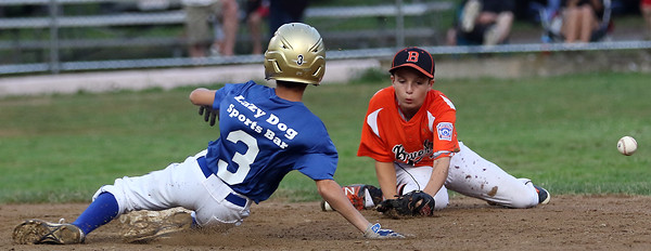 DAVID LE/Staff photo. The baseball bounces away from Beverly shortstop Griffin Francis as he tries to swipe a tag on Lynn's Anthony Marino (3). 8/16/16.