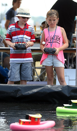 DAVID LE/Staff photo. Trystin Dunavin, 10, left, and Natalia Gillis, 10, both of Pittsfield, MA, steer remote control boats around a small pool at the Salem Heritage Festival on Saturday afternoon. 8/7/16.