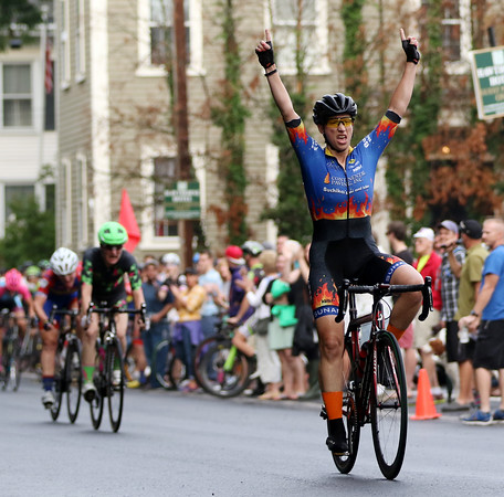 DAVID LE/Staff photo. Women's Elite racer Leslie Timm raises both arms over her head after she out kicked the field to the finish line to win the Women's Elite Witches' Cup race. 8/10/16.
