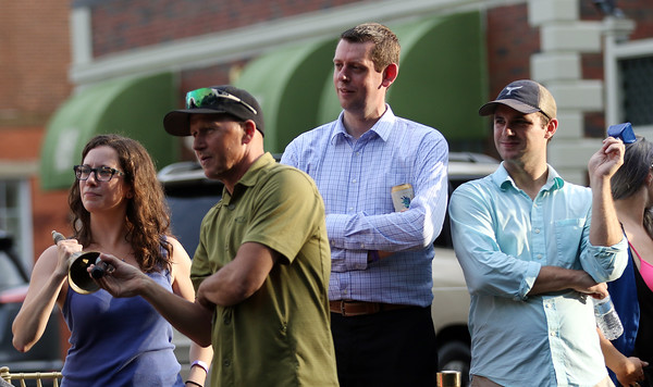 DAVID LE/Staff photo. Ward 2 City Councilor Heather Famico rings a bell to signal a premium lap, while Patrick Cornelisson, General Manager of the Hawthorne Hotel, and Andy Seidel, of Salem, cheer on racers during the annual Witches Cup on Wednesday evening. 8/10/16.