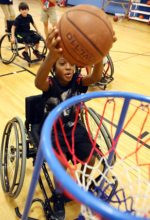 KEN YUSZKUS/Staff photo.    Jayvon Fortes shoots a basket during a basketball game while using a high-tech, modified wheelchair which was one of many Spaulding Rehab brought to try out.  08/04/16