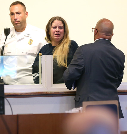 KEN YUSZKUS/Staff photo.    Emma Wiley, center, is the 19-year-old who bit off a piece of a Salem police officer's ear, is led out of the courtroom after being arraigned in Salem District Court.    08/08/16