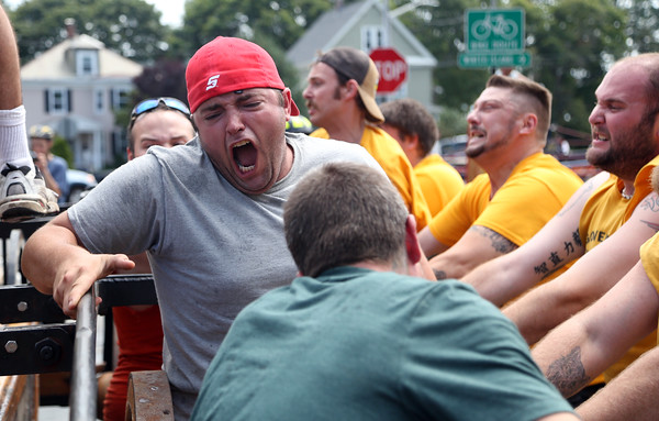 DAVID LE/Staff photo.Eric Fuller, of Barrington, NH, screams out to encourage his teammates as they try and pump as hard and fast as they can to shoot a stream of water out of an old fire engine. 8/7/16.