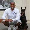 Jermaine Anderson poses with his doberman pinscher outside his new dog training business, Loyal Canines, Thursday, July 28, in Peabody.