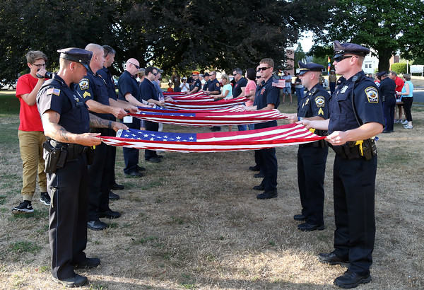 DAVID LE/Staff photo. Police and fire department members and local spectators volunteered to fold 16 American flags. 8/7/16.