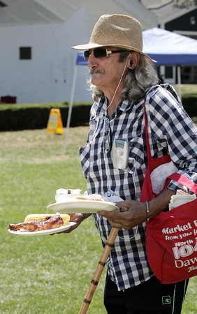 KEN YUSZKUS/Staff photo.   Jeffrey Alexander walks with plates of food toward the tables under the tent at the Lobster Fest held at Lynch Park.  08/03/16