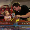DAVID LE/Staff photo. Two-year-old Gianna Dixon, of Peabody, left, smiles excitedly after winning tickets while playing a game with her uncle Luke Raphael, at the Salem Willows Arcade on Tuesday evening. 8/30/16.