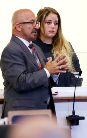 KEN YUSZKUS/Staff photo.    Emma Wiley stands with her attorney Mark Barry. She is the 19-year-old arraigned in Salem District Court for biting off a piece of a Salem police officer's ear.    08/08/16