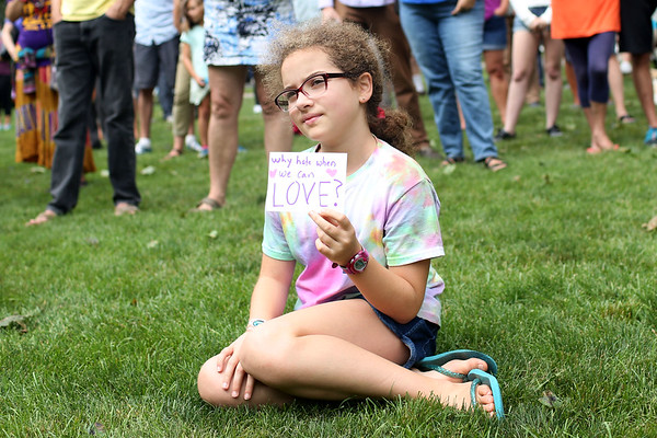 """HADLEY GREEN/Staff photo<br /> Mirand Cotter-Holland, 10, of Beverly, held a sign reading """"Why hate when we can love?"""" at the Rally for Love on Beverly Common. 8/18/17"""