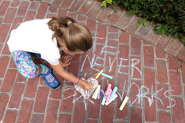 """HADLEY GREEN/Staff photo<br /> Emma Anderson of Beverly draws a heart next to a chalk message that reads """"Hate never works"""" on Beverly Common at the Rally for Love. 8/18/17"""