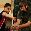 HADLEY GREEN/Staff photo<br /> Jayrian Morales, 6, of Lawrence, pulls the tape off the mouth of an American alligator at the Rainforest Reptiles show at the Flint Library in Middleton. 8/15/17