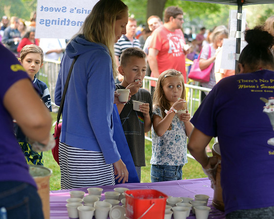 RYAN HUTTON/ Staff photo<br /> Gina Billings and her children Finn, 8, and Farren, 6, try some ice cream from Maria's Sweet Somethings at the Salem Heritage Days Ice Scream Bowl at the Salem Common on Tuesday.