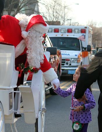 MARIA UMINSKI/SALEM NEWS Santa greets seven year-old Romie Randazzo of Wenham during the Holiday Parade in Beverly on Sunday.