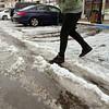 KEN YUSZKUS/Staff photo.   Mark Fantasia of Salem walks carefully through the slushy mixture created by the snow and rain this morning in Salem.   12/29/15.