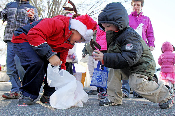Mateo Ibanez, 7, and Ben Malaquias, 4, both of Beverly collect candy thrown from floats during Beverly's 68th annual Holiday Parade Sunday, Nov. 29, as they march down Elliot Street.