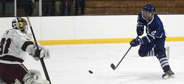 DAVID LE/Staff photo. Danvers sophomore Tom Mento fires a shot past Gloucester goalie Noah Poliskey (31). 12/12/15.