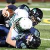 DAVID LE/Staff photo. Essex Tech junior Brendan Ahern (28_ and sophomore Alec Bolstad (40) drag down McCann Tech wide receiver Dakota Bolte. 12/3/15.