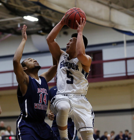 DAVID LE/Staff photo. Gordon junior point guard Jaren Yang (5) drives hard to the hoop and draws contact from Daniel Webster sophomore Tommy Organ (14). 12/10/16.