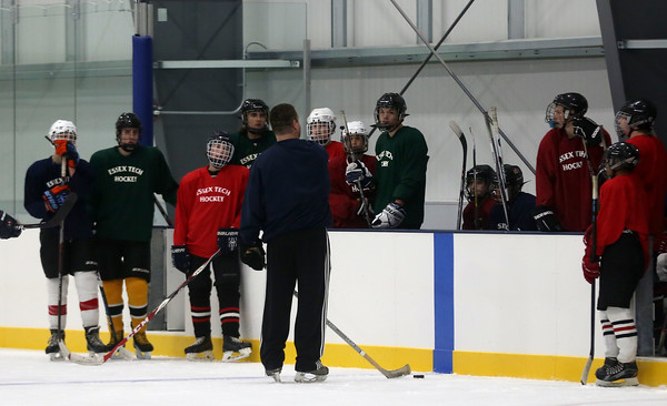 DAVID LE/Staff photo. Essex Tech boys hockey players listen to head coach Mike Geary at practice during the preseason. 12/8/16.