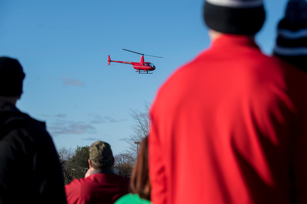 SAM GORESH/Staff photo. Runners watch a helicopter with Santa Claus and the Grinch landing before the Law Enforcement Torch Run at Analogic benefitting the Special Olympics. 12/4/16