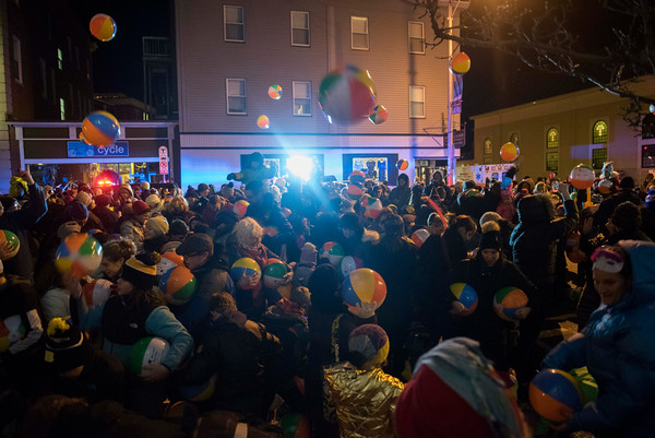 People drop beach balls from the second floor of the Montserrat College of Art and into the crowd during Beverly's New Year's celebration on Cabot Street. 12/30/16