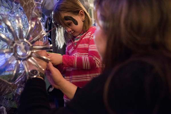 SAM GORESH/Staff photo. Fiona Krupkowski, 5 (left) and artist Linda Mullen (right) attach decorations made of recycled bottles on the New Year's ball at the Salem Main Streets' Launch New Year's Eve event at the Old Town Hall.  Mullen, owner of Grace and Diggs teamed up with Tommy Gagnon of Boston Woodworking to make the ball for the celebration. 12/31/16