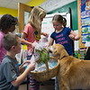 Jared Charney / Photo From L-R: Cameron Charest,7, Horace Mann Elementary 2nd Graders Francis Jones, 8, Annie Bednar, 7, Yeilani Ravelo, 7, & Joshua Rounds, 8 present a basket of hand man snowmen to therapy dog Patrick to be delivered to residents at the Kaplan House, Thursday, December 8, 2016.