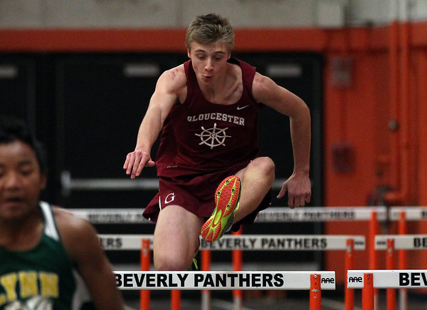 DAVID LE/Staff photo. Gloucester freshman Andrew Topouzoglou leaps over a hurdle in a meet against Lynn Classical at Beverly High School. 12/20/16