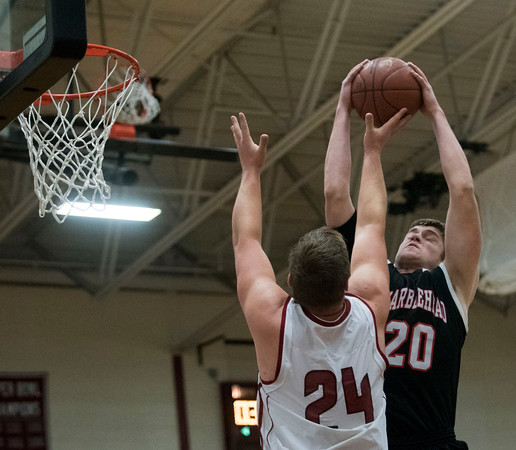 SAM GORESH/Staff photo. Marblehead junior Anson Clough Jr. grabs the ball away from Gloucester senior Ryan Gabriele in their game at at Gloucester High School. 12/16/16