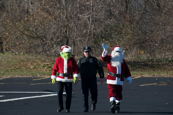 SAM GORESH/Staff photo. Officer Rick Heath escorts the Grinch and Santa Claus to after they road in on a helicopter Law Enforcement Torch Run at Analogic benefitting the Special Olympics. 12/4/16