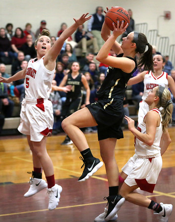 HADLEY GREEN/Staff photo<br /> Bishop Fenwick's Sammi Gallant (5) shoots while Masconomet's Paige Amyouny (5) plays defense at the Masconomet v. Bishop Fenwick girls basketball game at Masconomet High School.<br /> <br /> 12/23/17