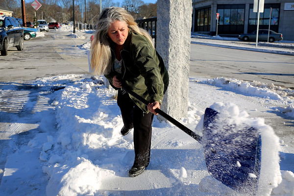 HADLEY GREEN/Staff photo<br /> Pamela Sherry-Landess shovels snow and ice off the sidewalk in front of her her business, Carroll's Florist. Sherry-Landess says her business has been negatively affected by the Rantoul Street construction, which has made snow removal difficult. <br /> <br /> 12/28/17