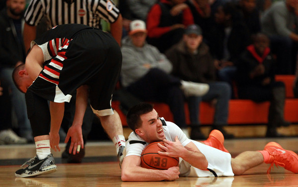 Beverly senior captain Chris Sinclair dives on the floor after stealing the ball from North Andover junior Brett Daley. DAVID LE/Staff photo 2/25/14