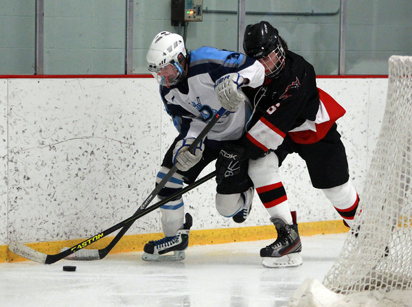 Salem junior defenseman Eli Spector (6) leans on Dracut junior forward Jack Brown (3) behind the Witches net during the second period of play on Thursday evening. DAVID LE/Staff Photo 2/27/14