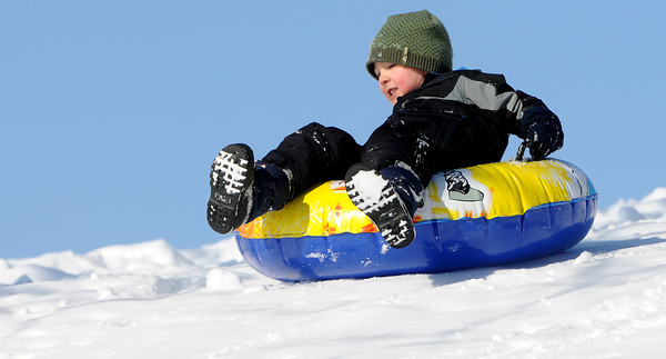 Ken Yuszkus/Staff photo: Beverly:  William Gavenas, 4, of Beverly, slides down a hill at Dane Street Beach on his tube.