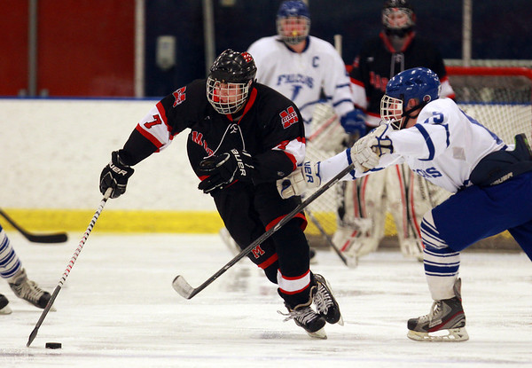 Marblehead sophomore center Matt Koopman shields the puck from Danvers junior defenseman Stephen Ganley (15)  while carrying the puck up ice on Wednesday evening. DAVID LE/Staff Photo 2/12/14