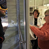 Beverly native Ed Robinson, left, eagerly peers at the printed tickets from Saturday's vote regarding the proposed Brimbal Ave Project, as they are taped to the window by Beverly City Clerk Kathy Connolly, center, and Fran Macdonald, from the Beverly Board of Registrars, on Saturday evening at Beverly High School. DAVID LE/Staff photo